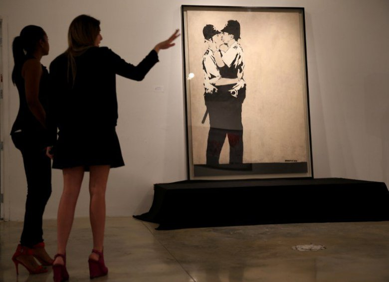 """Kissing Coppers"" de Banksy lors de sa vente aux enchères à Miami. / © JOE RAEDLE / GETTY IMAGES NORTH AMERICA / AFP"