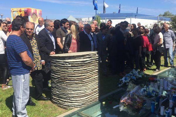 Des victimes, des familles de victimes et des anonymes réunis autour de la stèle au stade de Furiani, le 5 mai 2016.