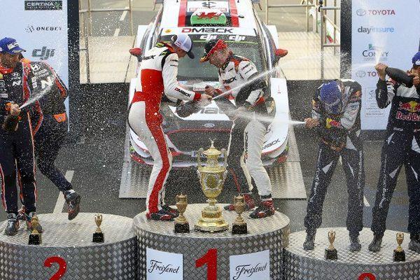 Sébastien Ogier et son co-pilote Julien Ingrassia sablent le champagne ( au centre de la photo)