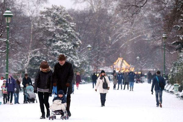 Des gens déambulent dans le parc Monceau sous la neige