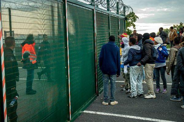 Des migrants tentant de franchir les grilles du site d'Eurotunnel, fui