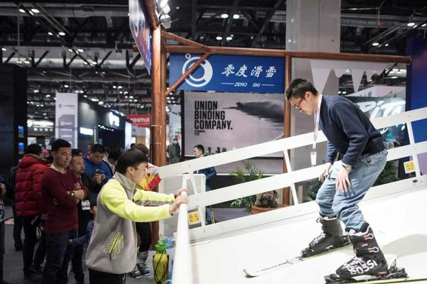 "Un homme sur un simulateur de ski à l"" International Trade Show for Mountain and Winter Technologies"" à Pékin, le 15 février 2017."