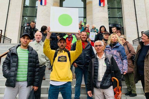 """Sur les marches du tribunal de Rodez, des représentants du collectif des """"ronds verts"""" affichent leur soutien"""