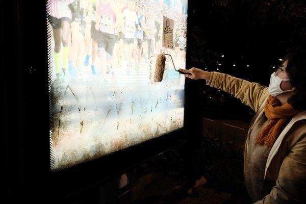 Une militante recouvre de blanc de Meudon une publicité lumineuse.