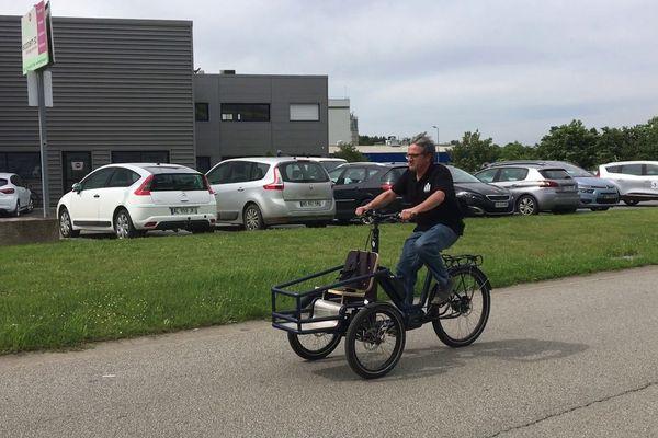 Michel Bertrand sur son vélo triporteur pendulaire, un triporteur qui s'incline dans les virages comme un vélo pour en faciliter la conduite