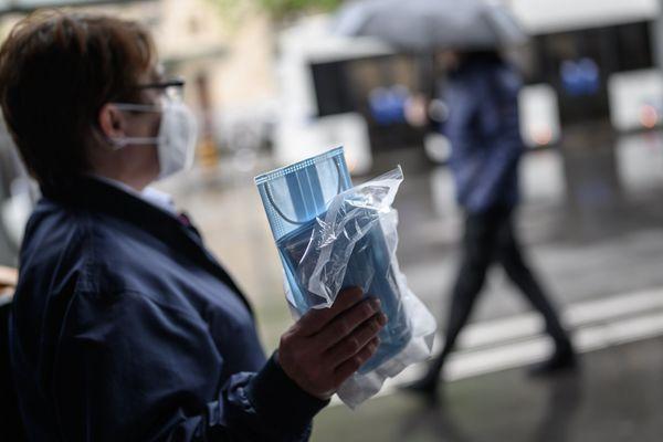 Une employée distribuant des masques chirurgicaux dans les transports publics de Lausanne, en Suisse.