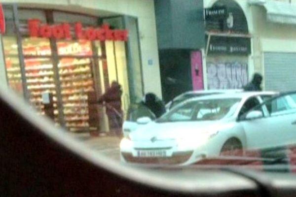 Les braqueurs repartent en voiture après le braquage filmés par un passant avec son téléphone.