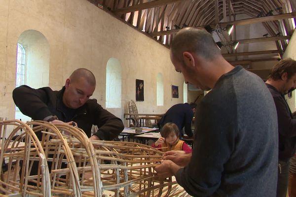 Des dizaines de personnes participent à la création d'une marionnette géante faite d'osier et de fil de fer.