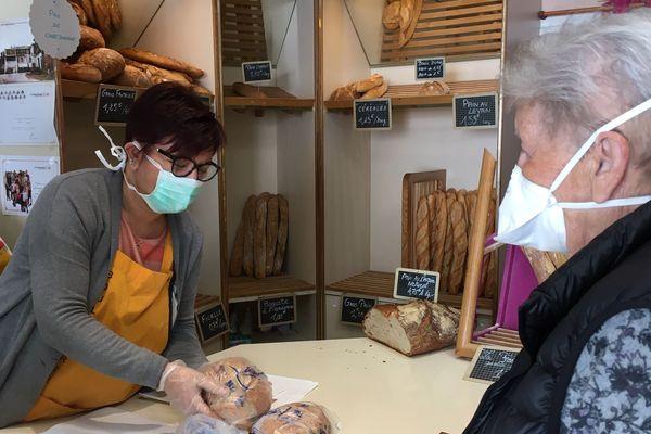 La boulangère porte masque et gants pour servir le pain aux clients du village.