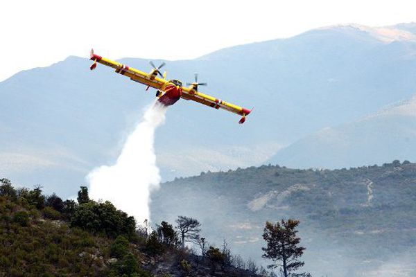 Un Canadair effectue un largage au-dessus d'un feu - Illustration.