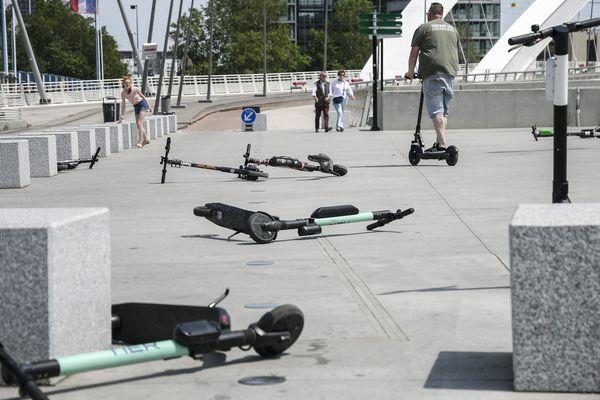 Trottinettes mal garées et couchées au sol à Lyon, sur l'esplanade du musée des Confluences. Dans cette ville, une charte de bonne conduite encadre l'usage de ces engins, s'appuyant sur la loi sur les mobilités.