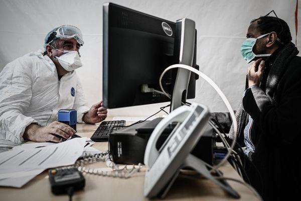 Un médecin généraliste reçoit en consultation, pendant l'épidémie de coronavirus.