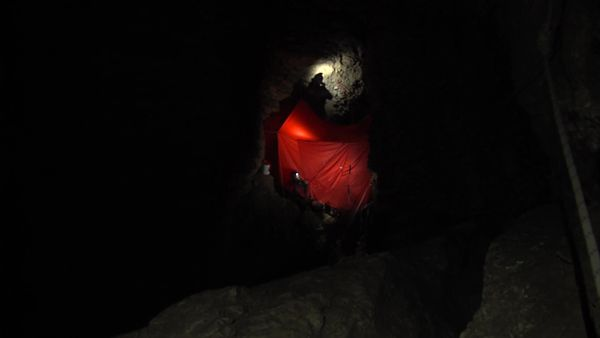 Dans l'obscurité de la grotte on distingue la tente médicale éclairée par les frontales