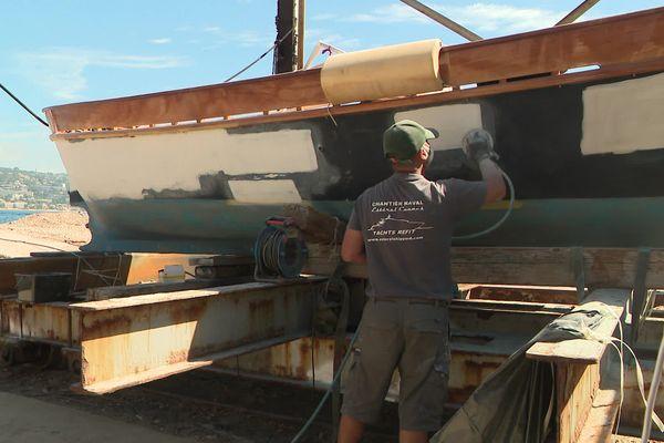 Un ouvrier du chantier naval de l'Estérel travaille sur un bateau.