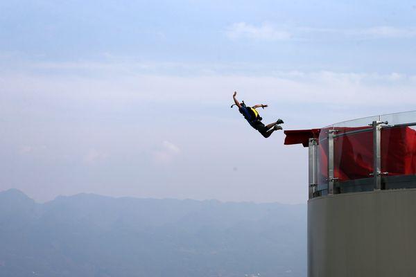 Exemple de saut en Chine en 2017. Le BASE jump est un sport extrême consistant à sauter depuis des objets fixes équipé d'un parachute et non depuis des aéronefs. Il combine d'autres disciplines (parachutisme, parapente, alpinisme, précision d'atterrissage, voltige, etc.)