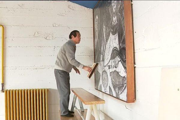 Le professeur Tetsuyu Shiraishi de Tokyo lors de la mise en place dans l'abri du pèlerin de nouvelles reproductions tirées au Japon.