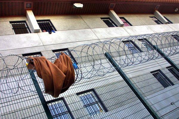 Des détenus, à la fenêtre, regardent une couverture envoyée sur les barbelés - Photo d'illustration