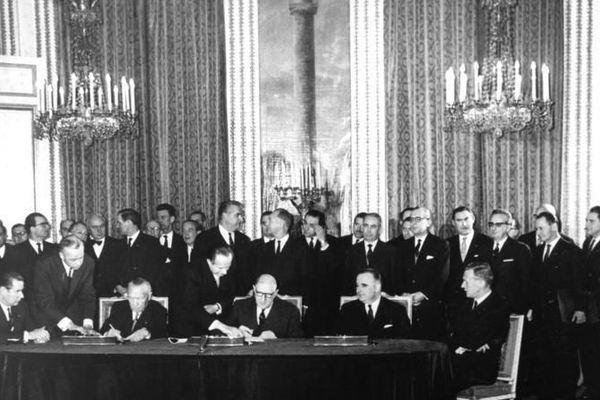 Konrad Adenauer (chancelier ouest-allemand), Charles de Gaulle (président français), Georges Pompidou (chef du gouvernement français), Maurice Couve de Murville (ministre français des affaires étrangères), et Gerhard Schröder (ministre ouest-allemand des affaires étrangères) attablés pour la signature du traite de l'Élysée en 1963.