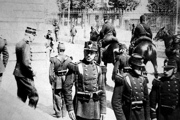 Photo d'archive prise en septembre 1899 du capitaine Alfred Dreyfus à la sortie du procès de Rennes, entre deux rangées de militaires qui lui tournent le dos.