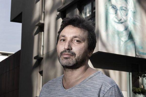 L'artiste C215 devant le portrait de Soeur Emmanuelle réalisé en 2017 à Paris