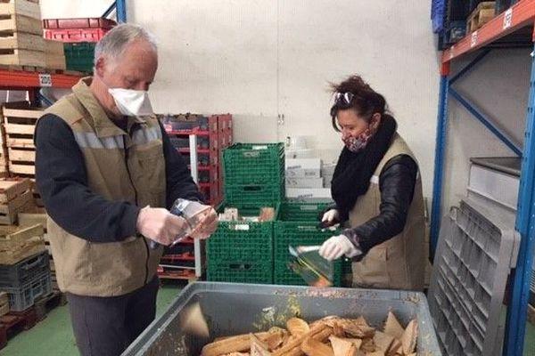 Deux nouveaux bénévoles trient des marchandises périmées pour les recycler les emballages et nourrir des animaux d'élevage.