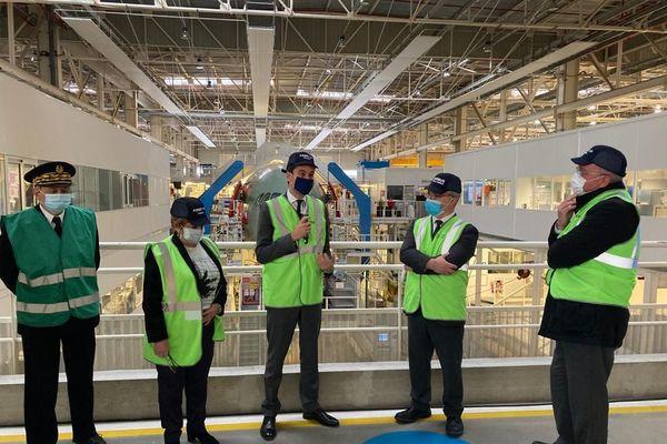 Gabriel Attal, ici au centre tenant le micro, en visite dans les ateliers Airbus.