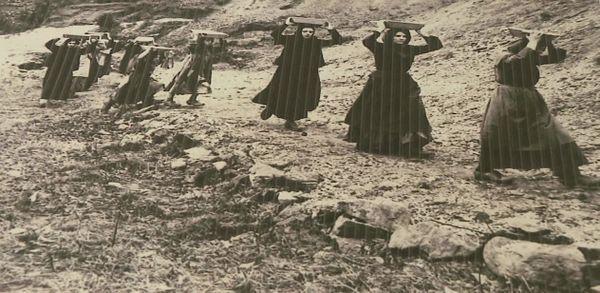Femmes remontant sur leur tête les pierres de kaolin avant de les trier