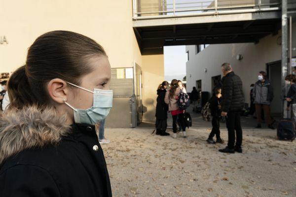Élève masquée devant une école primaire.