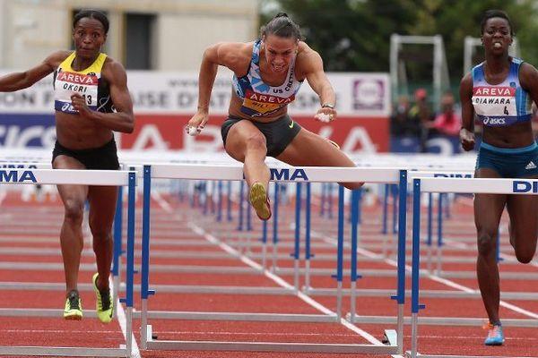 Reina Flor Okori (à gauche) termine deuxième de la finale du 100m haies aux Championnats de France d'athlétisme à Reims, battue par Cindy Billaud (au centre), le 12 juillet 2014.
