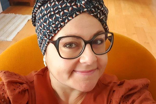 Emilie avec un turban, qu'elle a adopté pendant ses traitements contre le cancer. Elle a créé le site Miochi pour permettre la revente des accessoires dont on a besoin pendant la maladie.