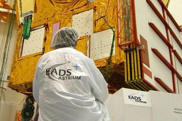 Un technicien travaillant sur un satellite Hélios