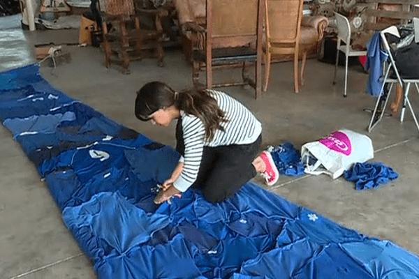 Samia Ziadi finalise la manche de quatre mètres de long qui est composée de tee-shirts bleu qui ont été portés