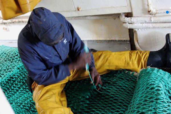 Un pêcheur sénégalais en train de réparer un filet au large de Port en Bessin (Calvados).