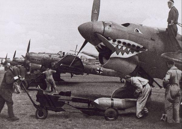 """Chargement des bombes sur des Junkers Ju 87 """"Stukas"""" sur un aérodrome du nord de la France en 1940."""