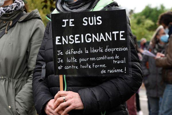 Une enseignante ce samedi 17 octobre à Conflans-Saint-Honorine, à proximité du lieu où un professeur d'histoire-géographie a été assassiné vendredi.