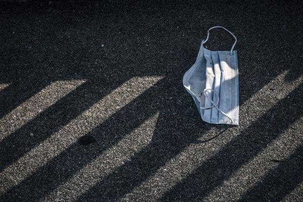 Un masque chirurgical abandonné sur le sol.