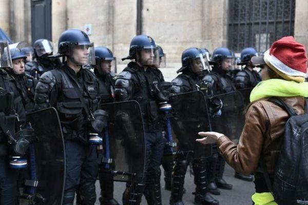 """Des membres des forces de l'ordre font face à une manifestante lors d'un rassemblement de """"gilets jaunes"""" à Paris, le 11 décembre 2018."""