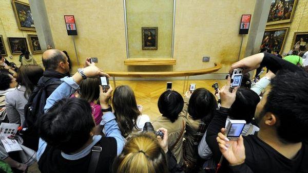 La Joconde entourée de touristes au musée du Louvre à paris.