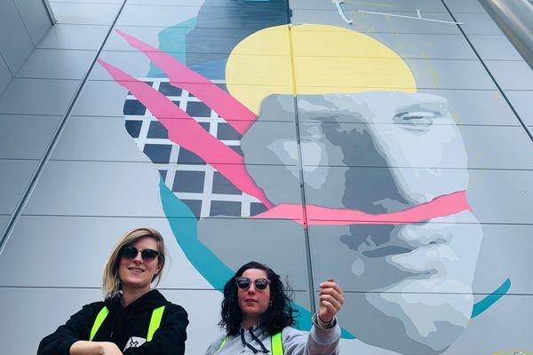 Les artistes rémoises Mat et Zekky, en haut de leur nacelle face à leur fresque en Seine-et-Marne.