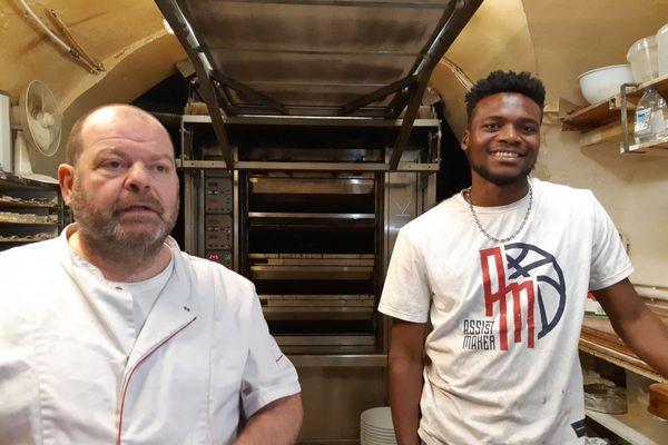 """Le boulanger Stéphane Ravacley et son apprenti Laye Fodé Traoré à l'intérieur de la boulangerie """"La Huche à pain""""."""