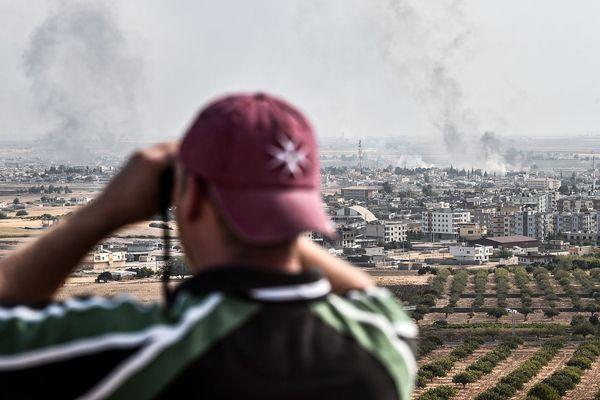 Depuis la ville turque de Sanliurfa, un homme regarde aux jumelles les panaches de fumées au-dessus de la ville syrienne de  Ras al-Ain, de l'autre côté de la frontière.