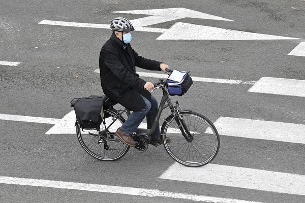 Un homme portant un masque fait du vélo.
