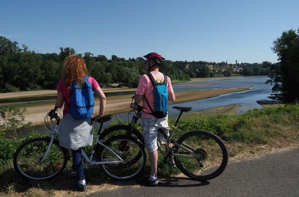 """Deux cyclistes regardent la Loire sur la route appelée """"Loire à Velo"""" à Saint-Pierre-des-Corps, près de Tours. La """"Loire a velo"""" c'est 900 km de piste cyclable allant de Cuffy près de Nevers à Saint-Brevin-les-Pins en Loire-Atlantique. La France est la seconde destination au monde du tourisme cyclable avec près de  16,000 km d'itinéraires à parcourir."""