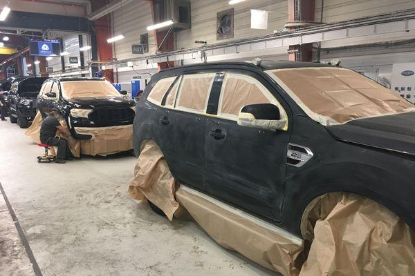 Le véhicule est préparé par les agenceurs avant de passer en cabine de peinture.