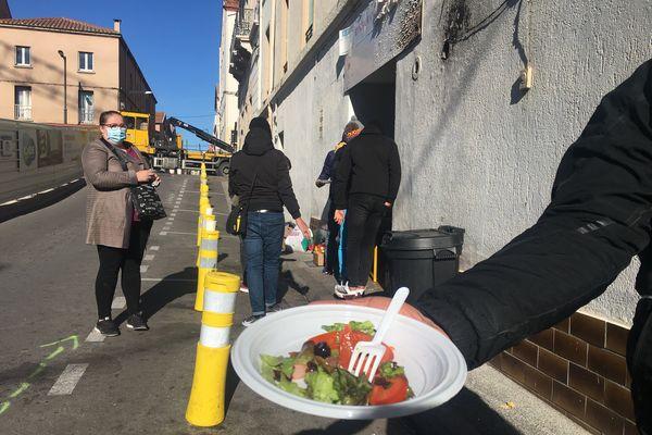 Les associations servent des repas dans la rue aux SDF et aux Sans Papiers près de la gare de Perpignan