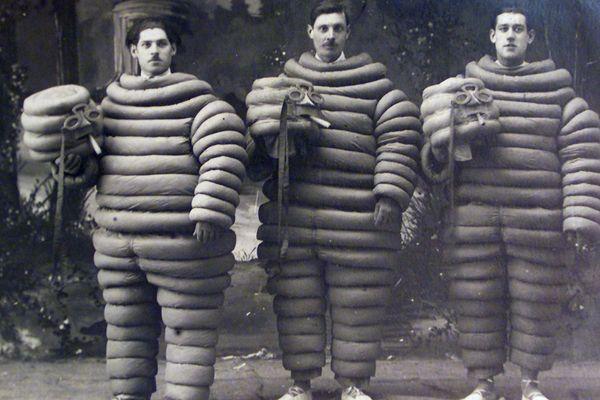Une reproduction d'une carte postale de 1920, sur laquelle trois ouvriers de l'usine Michelin posent en costume de Bibendum.