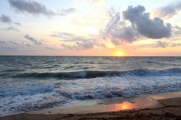 Nuages et soleil couchant à l'horizon face à la plage d'Agon-Coutainville, dans la Manche.