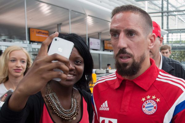 L'attaquant français du Bayern de Munich Franck Ribéry pose pour la photo avec des fans à l'aéroport de Munich. Le 30 juillet 2014.