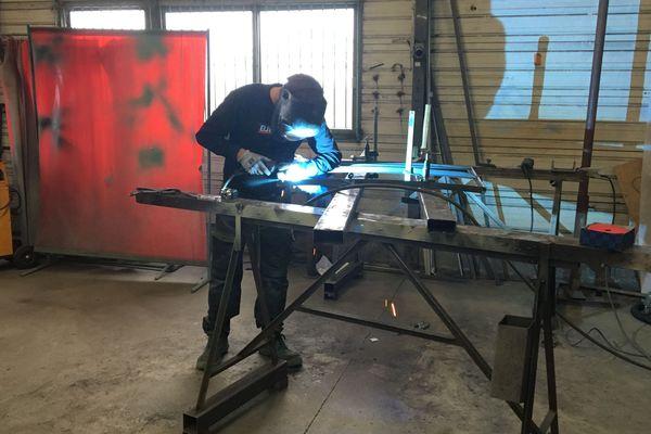 Un ouvrier travaille l'acier dans l'atelier de Serres d'antan.