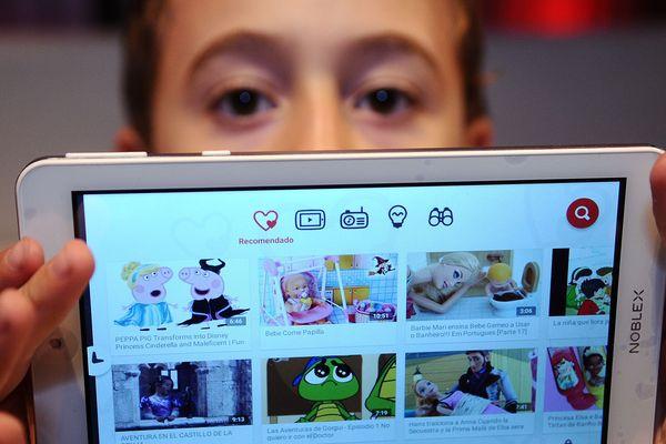 Un enfant montre son application Youtube sur sa tablette - Photo d'illustration